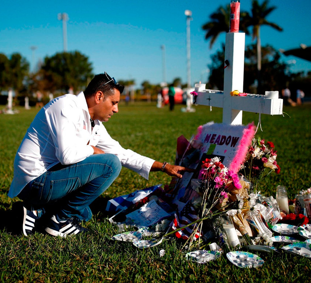 Joe Zevuloni mourns in front of a cross placed in a park to commemorate the victims of the shooting at Marjory Stoneman Douglas High School, in Florida. Photo: Reuters