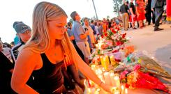 A student places a candle with other tributes during a vigil after Nikolas Cruz murdered 17 people. Photo: Reuters. Photo: Jonathan Drake/Reuters