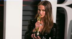 Alicia Vikander holds her Oscar for best supporting actress in her role