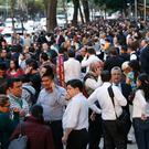People stand along Reforma Avenue after a 7.2-magnitude earthquake shook Mexico City, Friday, Feb. 16, 2018. (AP Photo/Marco Ugarte)