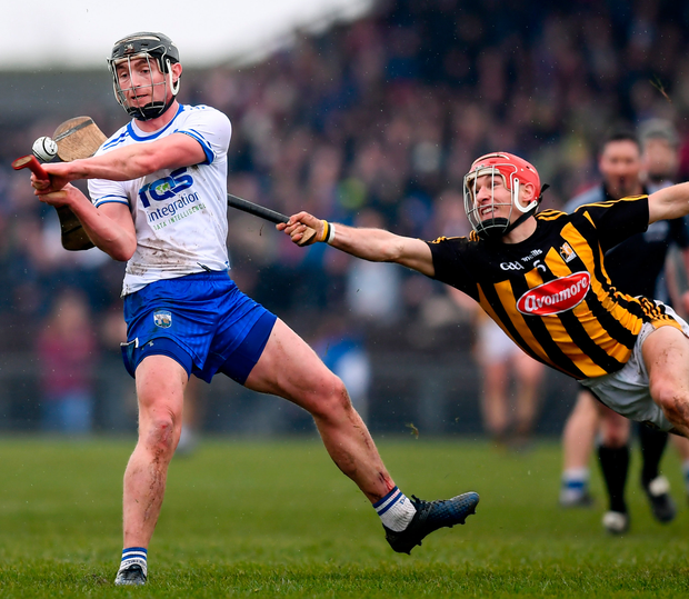 Waterford's Pauric Mahony gets his shot away despite the attention of Kilkenny's Cillian Buckley during the Allianz NHL clash in Walsh Park. Photo: Sportsfile