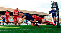 James Lowe goes over to score one of his two tries despite the tackle of Corey Baldwin of Scarlets. Photo by Seb Daly/Sportsfile