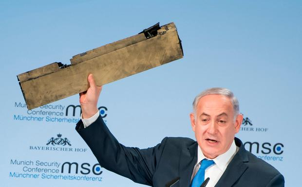 Israeli Prime Minister Benjamin Netanyahu holds up a remnant of what he said was a piece of Iranian drone shot down in Israeli airspace. Photo: Lennart Preiss/MSC Munich Security Conference/Handout via REUTERS