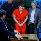 A video monitor shows school shooting suspect Nikolas Cruz, left, with public defender Melisa McNeille, making an appearance before Judge Kim Theresa Mollica in Broward County Court, Fort Lauderdale, Fla. (Susan Stocker/South Florida Sun-Sentinel via AP, Pool)