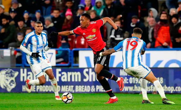 Manchester United's Anthony Martial (centre) skips away from Huddersfield Town's Danny Williams. Photo credit: Martin Rickett/PA Wire