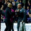 Manchester City manager Pep Guardiola (left) exchanges heated words with Wigan Athletic manager Paul Cook