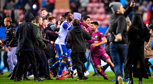 Sergio Aguero of Manchester City is surrounded by fans as he attempts to leave the pitch