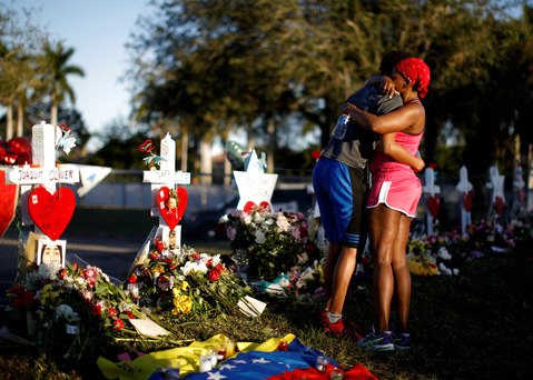Mourners embrace in front of the fence of the school to commemorate the victims of the shooting at Parkland, Florida. Photo: Reuters