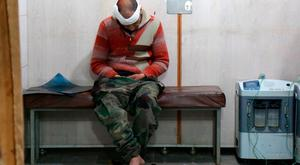 A Syrian man waits to receive treatment at a make-shift hospital in Kafr Batna following government air strikes on the town of Jisreen, in the besieged Eastern Ghouta region on the outskirts of the capital Damascus, on February 19, 2018. AFP PHOTO / Ammar SULEIMANAMMAR SULEIMAN/AFP/Getty Images