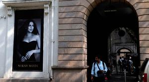 A man walks in front of a Nirav Modi jewelry boutique, that displays a black and white photograph of Bollywood actress Priyanka Chopra in Mumbai, India (AP Photo/Rajanish Kakade)
