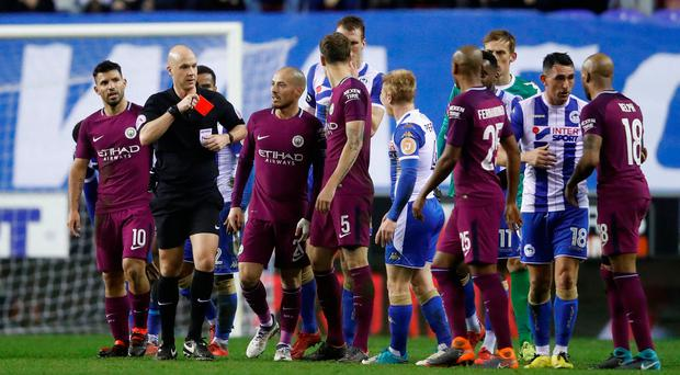 Manchester City's Fabian Delph is shown a red card by referee Anthony Taylor