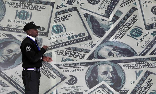 A security guard walks past a montage of U.S. $100 dollar bills outside a currency exchange bureau in Kenya's capital Nairobi