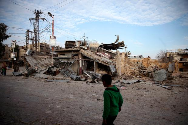 A child walks near damaged buildings in the besieged town of Douma, Eastern Ghouta, Damascus, Syria February 20, 2018. REUTERS/Bassam Khabieh