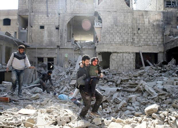 A man carries an injured boy as he walks on rubble of damaged buildings in the rebel held besieged town of Hamouriyeh, eastern Ghouta, near Damascus, Syria February 21, 2018. REUTERS/Bassam Khabieh