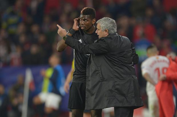 Jose Mourinho, Manager of Manchester United speaks to Paul Pogba during the UEFA Champions League Round of 16 First Leg match between Sevilla FC and Manchester United at Estadio Ramon Sanchez Pizjuan