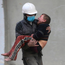 A member of the Syrian Civil Defense group carries a boy who was wounded during airstrikes Photo: AP
