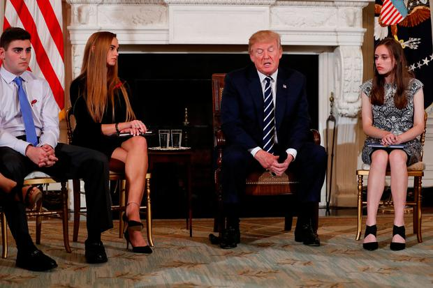 U.S. President Donald Trump, seated with Marjory Stoneman Douglas High School shooting surviving students Jonathan Blank (L), Julia Cordover (2nd L), and Carson Abt (R), delivers remarks during a listening session with Marjory Stoneman Douglas High School shooting survivors and students at the White House in Washington, U.S., February 21, 2018. REUTERS/Jonathan Ernst
