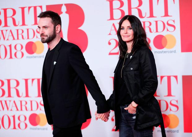 Courtney Cox and Johnny McDaid arrive at the Brit Awards at the O2 Arena in London, Britain, February 21, 2018. REUTERS/Eddie Keogh
