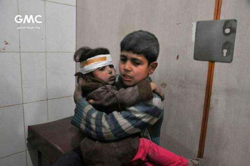 Two Syrian kids who were wounded during airstrikes and shelling by Syrian government forces sit at a makeshift hospital in Ghouta suburb of Damascus Syria