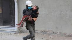 In this photo released on Wednesday Feb. 21, 2018, provided by the Syrian Civil Defense group known as the White Helmets, shows a member of the Syrian Civil Defense group carries a boy who was wounded during airstrikes and shelling by Syrian government forces, in Ghouta, a suburb of Damascus, Syria. . (Syrian Civil Defense White Helmets via AP)