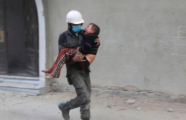 Member of the Syrian Civil Defense group carries a boy who was wounded during airstrikes and shelling by Syrian government forces, in Ghouta, a suburb of Damascus, Syria. . (Syrian Civil Defense White Helmets via AP)