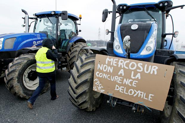 French farmers drive their tractors on the A7 highway to protest changes in underprivileged farm area's mapping and against Mercosur talks, in Pierre-Benite near Lyon, France, February 21, 2018. Message reads