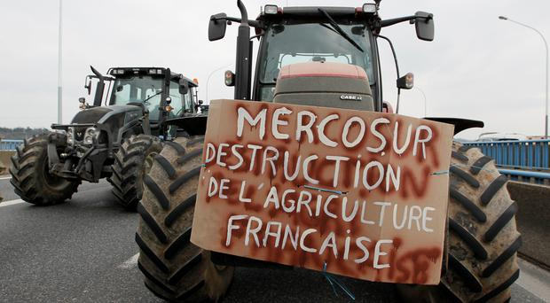 French farmers drive their tractors on the A7 highway to protest changes in underprivileged farm area's mapping and against Mercosur talks, in PIerre-Benite near Lyon, France, February 21, 2018. Message reads,