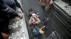 Syria Civil Defence members help an unconscious woman from a shelter in the besieged town of Douma, Eastern Ghouta, Damascus, Syria February 22, 2018. REUTERS/Bassam Khabieh