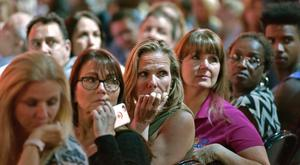 Adults watch a monitor honoring the 17 students and teachers killed at Douglas High School during a CNN town hall meeting, at the BB&T Center, in Sunrise, Florida, U.S. February 21, 2018. REUTERS/Michael Laughlin/Pool