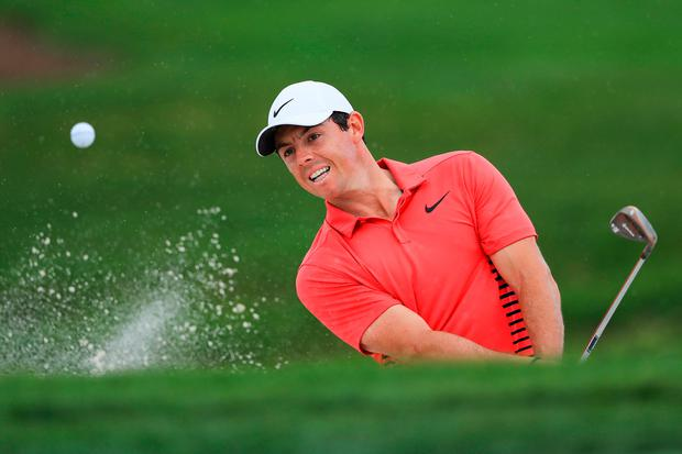 Rory McIlroy plays a shot out of a bunker on the third hole
