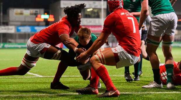 Jonny Stewart of Ireland is tackled short of the try line by Max Williams, left, and James Botham of Wales. Photo: Sportsfile
