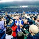 Dan Burn is mobbed by fans after Wigan Athletic's win over Manchester City in the fifth round of the FA Cup at the DW Stadium last Monday. Photo: Martin Rickett/PA