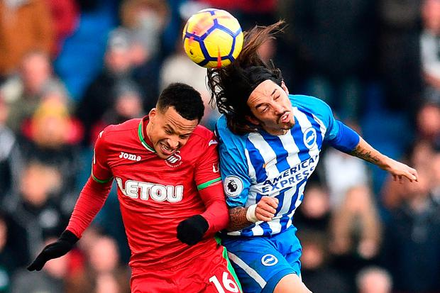 Brighton's Argentine-born Italian defender Ezequiel Schelotto (R) vies with Swansea City's Swedish defender Martin Olsson Photo:AFP/Getty