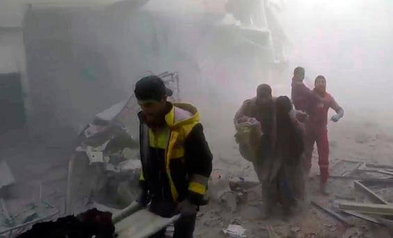 Members of the Syrian Civil Defense group help residents during airstrikes and shelling by Syrian government forces, in Ghouta, a suburb of Damascus, Syria. (Syrian Civil Defense White Helmets via AP)