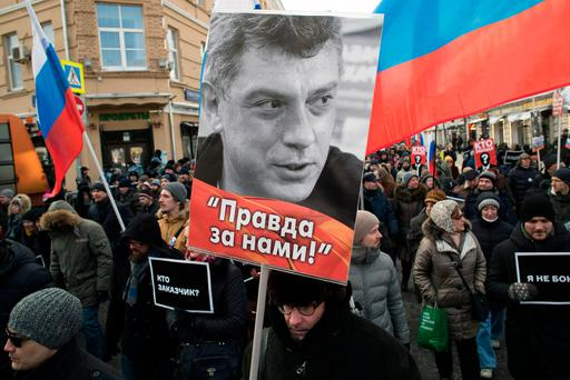 A man carries a portrait of slain opposition leader Boris Nemtsov during a march marking the three-year anniversary of his killing, in Moscow, Russia. Thousands of Russians took to the streets of downtown Moscow to mark three years since Nemtsov was gunned down outside the Kremlin. (AP Photo/Pavel Golovkin)