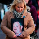 Emma Rogan holds a photo of her father Adrian, who was shot dead in Loughinisland in 1994, during a protest by survivors and relatives of those killed in the Troubles in Belfast. Photo: PA