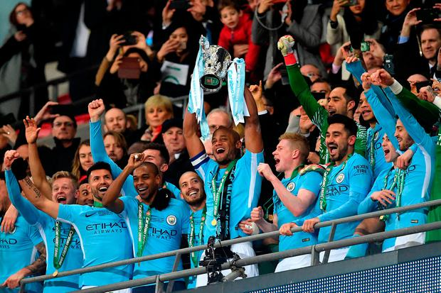 Vincent Kompany lifts the cup as Manchester City celebrate their victory at Wembley. Photo: PA Wire