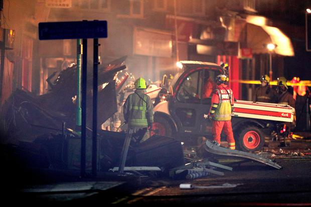 Emergency personnel load a small truck with debris at the scene on Hinckley Road in Leicester, after a