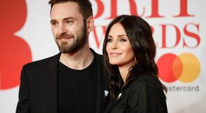 British singer Johnny McDaid (L) and partner US actress Courteney Cox pose on the red carpet on arrival for the BRIT Awards 2018 in London