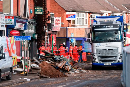 Emergency personnel continue to work at the scene on Hinckley Road in Leicester, where four people were killed, after a suspected explosion and subsequent fire destroyed a shop. Joe Giddens/PA Wire