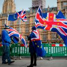 Anti-Brexit demonstrators protest with flags outside the Houses of Parliament in London, England. Photo: Getty Images