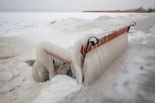 Ice covers a bench on the shore of Lake Balaton in Balatonfenyves, 155 kms southwest of Budapest, Hungary, as extreme cold strengthened by high winds chills most of Hungary. (Gyorgy Varga/MTI via AP)