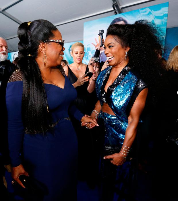 Cast member Oprah Winfrey and actor Angela Bassett greet each other at the premiere of