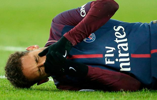 Paris Saint-Germain's Neymar lies on the pitch after sustaining an injury. REUTERS/Stephane Mahe