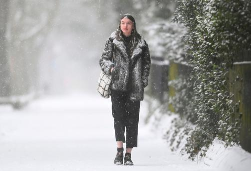 A woman walks along a snow covered path in Norwich, following heavy overnight snowfall which has caused disruption across Britain. Photo credit should read: Joe Giddens/PA Wire