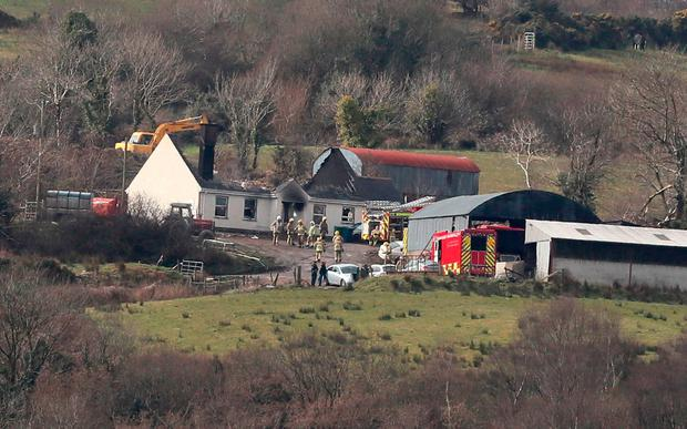 Emergency services at a house in Derrylin, Fermanagh where three people have died in a fire and police have arrested a man at the scene. Brian Lawless/PA Wire