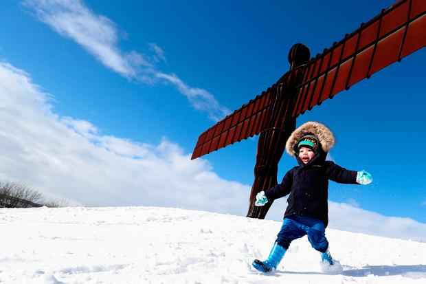 A boy plays in the snow next to the Angel of the North statue near Gateshead, Britain, February 27, 2018. REUTERS/Scott Heppell