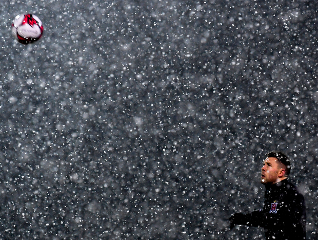 Dundalk defender Brian Gartland warms up as the snow falls at Oriel Park ahead of their game against Limerick last night. Photo: Sportsfile