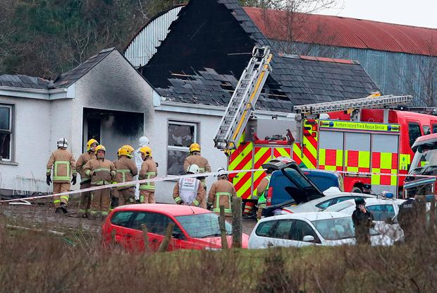 Forensic and fire officers at the house in Derrylin, Co Fermanagh, where four people died in a fire. Photo: Brian Lawless/PA Wire