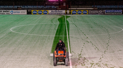 A member of the Oriel Park ground staff clears snow from the pitch prior to Tuesday's game between Dundalk and Limerick. Photo: Sportsfile